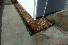 Landscaping border traps water from gutter and forces water into crawlspace