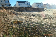 Extensive erosion from a sandy hill caused excessive soil buildup on side of a slab home